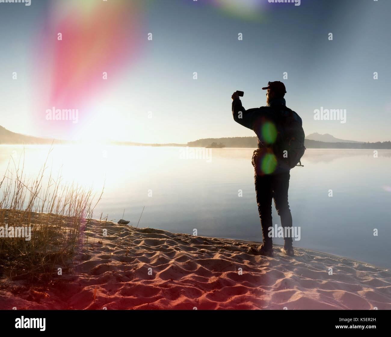 Tall caminante en la oscuridad sportswear con bastones y mochila deportiva a pie de playa. El turista disfrute de la salida del sol en el horizonte con un cielo azul sin nubes, llamarada solar. Imagen De Stock