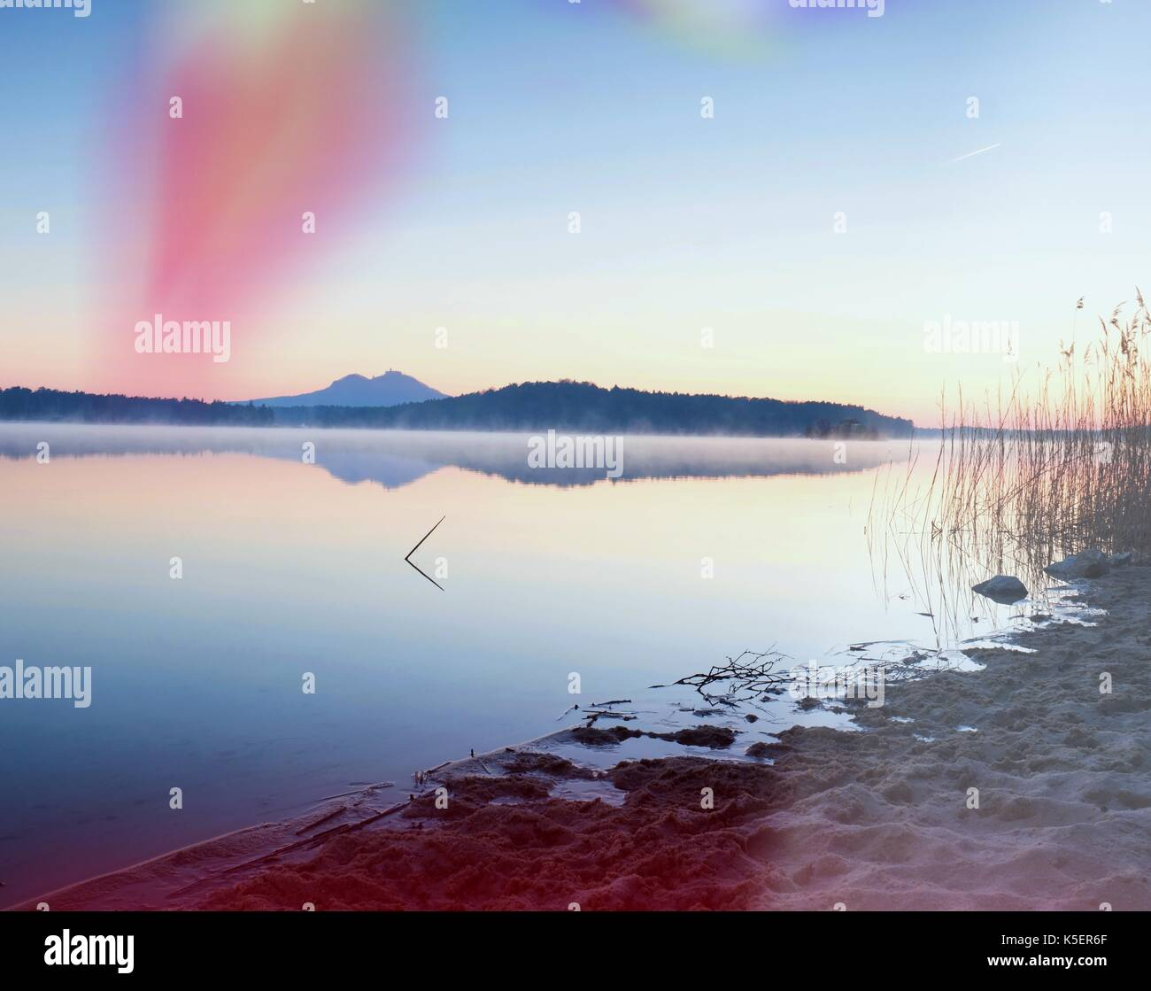 Hermoso amanecer en playa vacía, isla del mar mediterráneo. Tranquilo nivel de agua hace de espejo azul Foto de stock