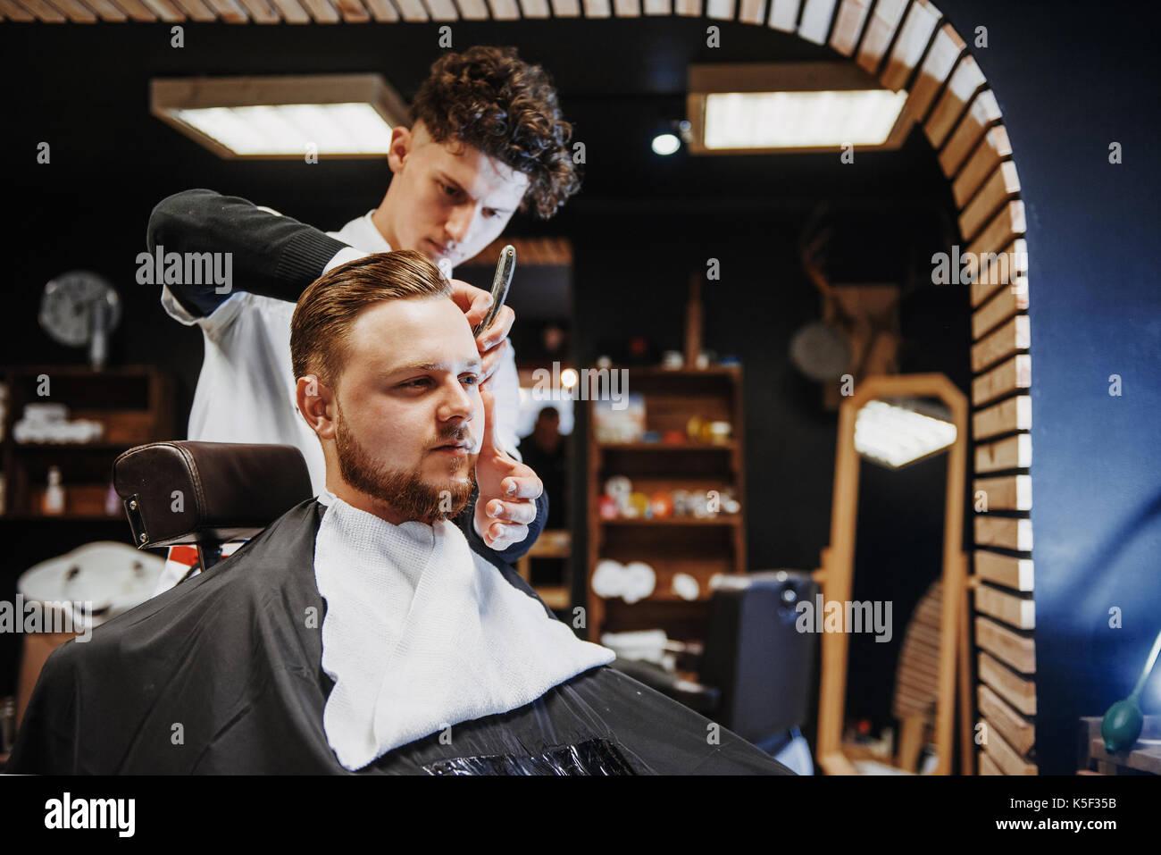 Hombre de peinado y peluquería en una barbería o peluquería. Imagen De Stock