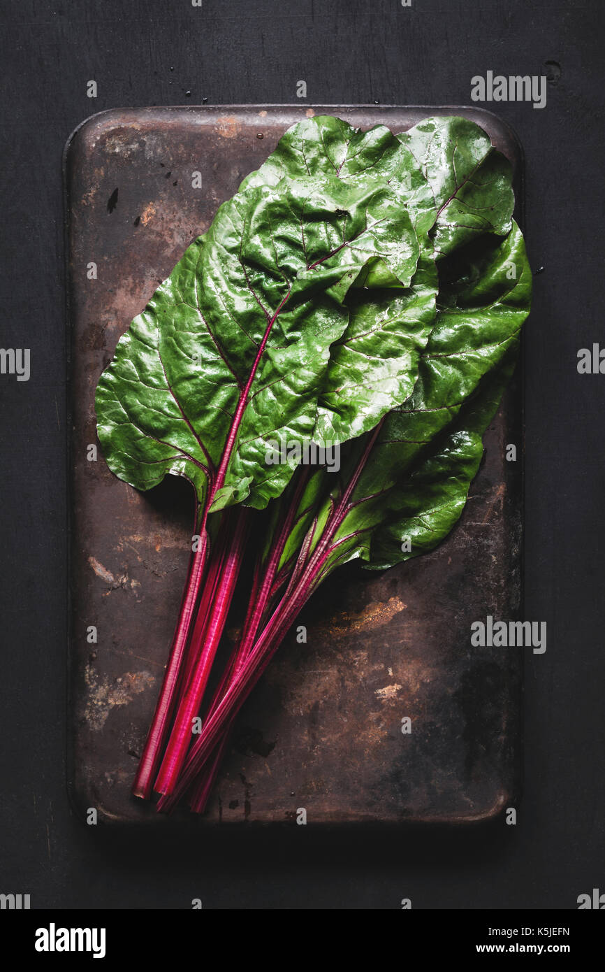 Las hojas de acelga fresca oxidado oscuro fondo. Vista superior de la mesa verde de alimentos orgánicos frescos Imagen De Stock