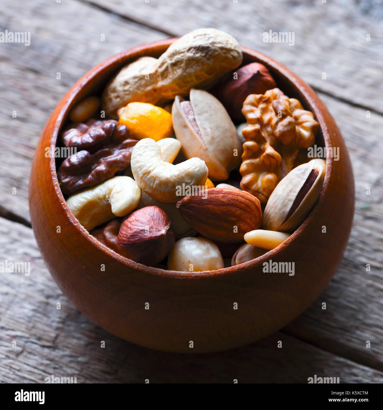 Mezcla de frutos secos en el recipiente de madera Imagen De Stock