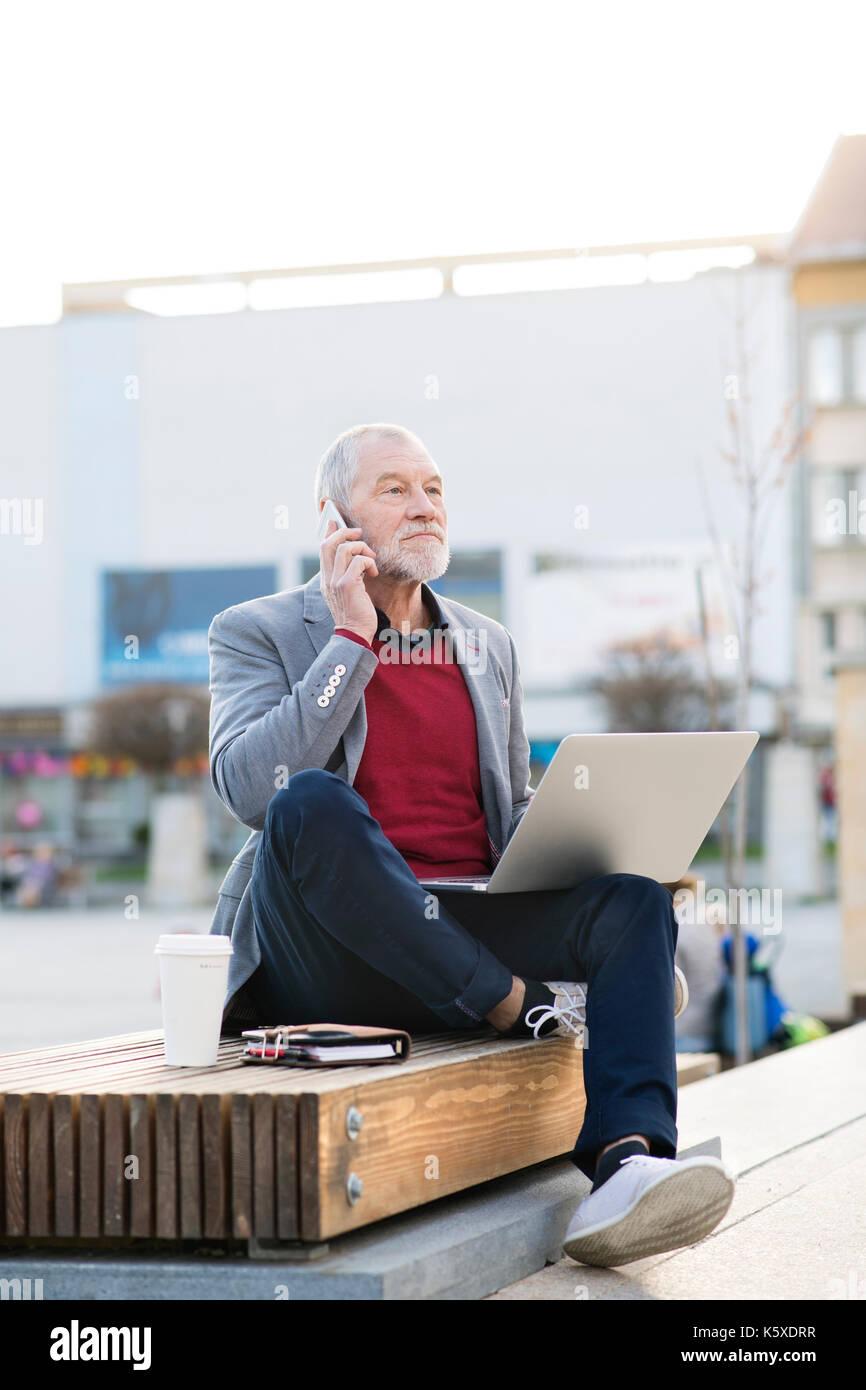 Hombre senior en la ciudad con un teléfono inteligente, realizar llamadas telefónicas Imagen De Stock