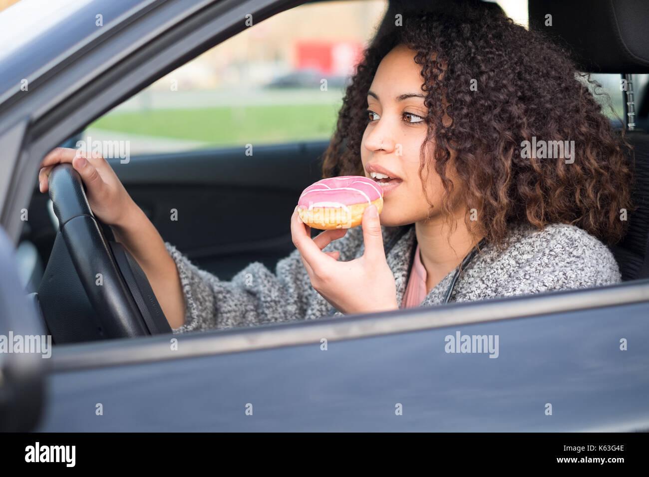 Mujer de comer un dulce conduce su coche Imagen De Stock