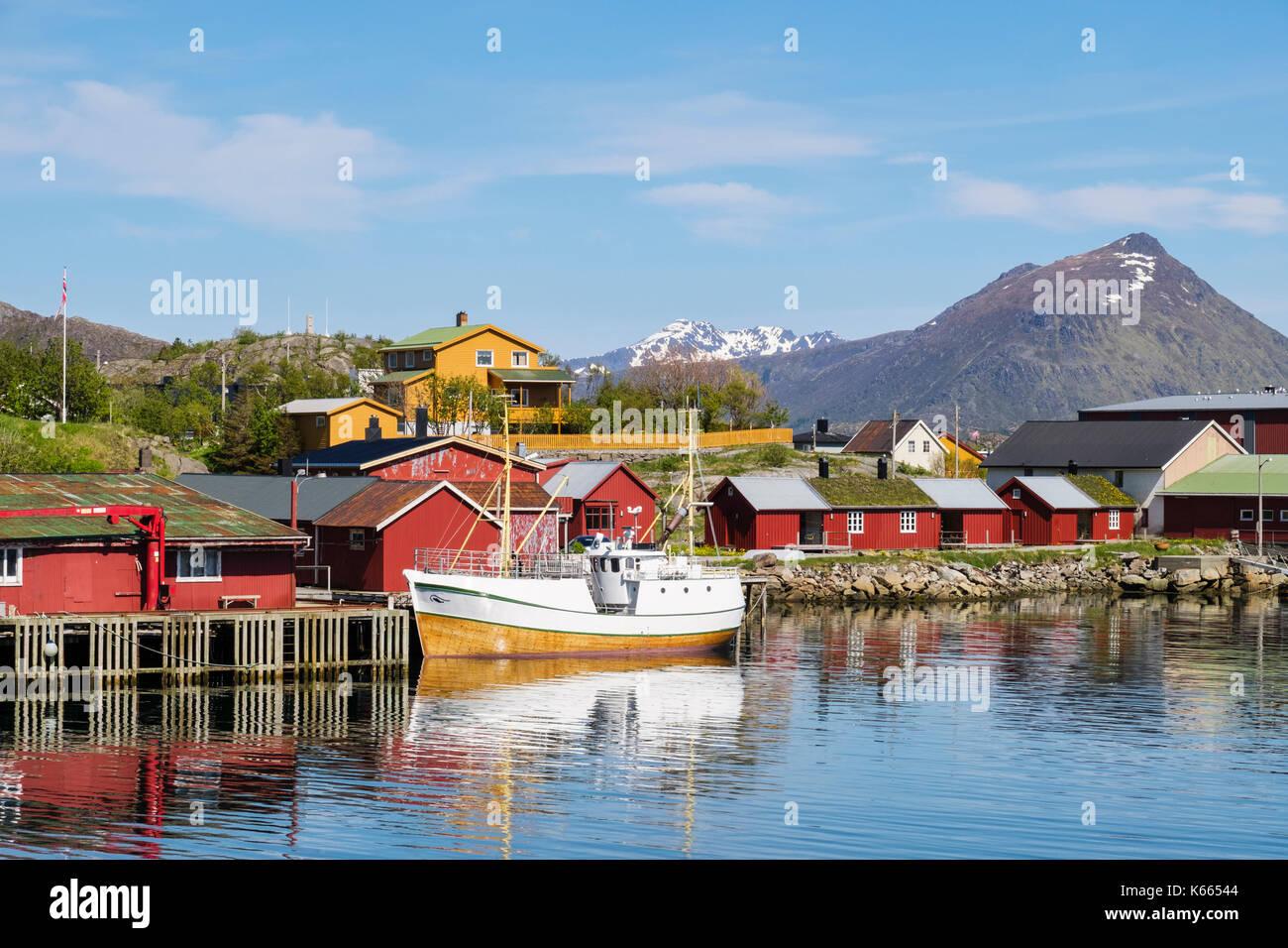 Barco anclado en el puerto con típicas cabañas Rorbu Noruego en la aldea de pescadores. Vestvågøya Ballstad, isla, Islas Lofoten, Nordland, Noruega Imagen De Stock