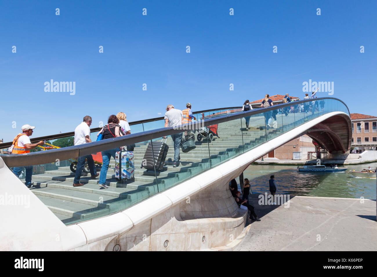 Los turistas cruzando el puente de Calatrava o el Ponte della Costituzione, Venecia, Italia cargando sus siutcases acompañado por dos hotel portaequipajes, Th Imagen De Stock