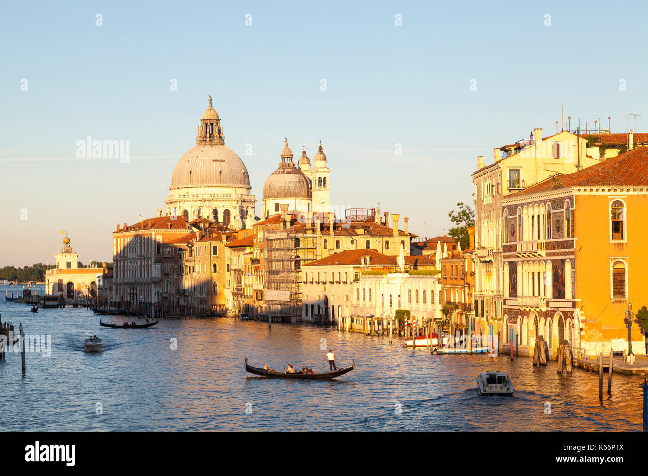 Atardecer sobre el Gran Canal y la Basílica de Santa Maria della Salute, en Venecia, Italia, con una góndola y barcos en el canal. Hora dorada luz cálida. Imagen De Stock