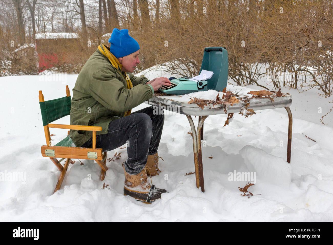 Un escritor sentado en una mesa en el exterior durante una tormenta de nieve y escribiendo en una máquina de escribir. Imagen De Stock