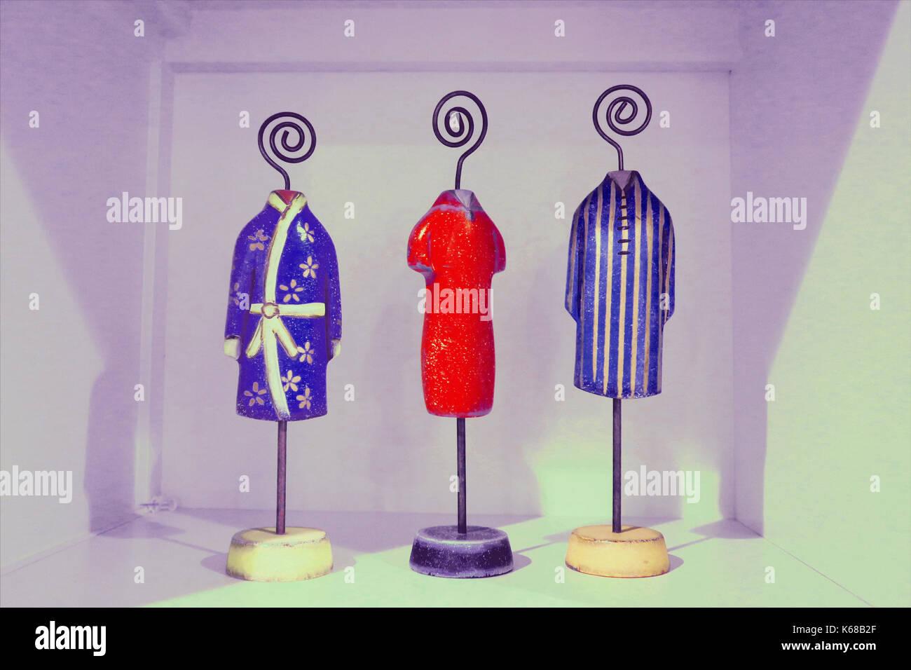 Tres soportes de tela decorativa en miniatura con una túnica y dos camisas. Foto de stock
