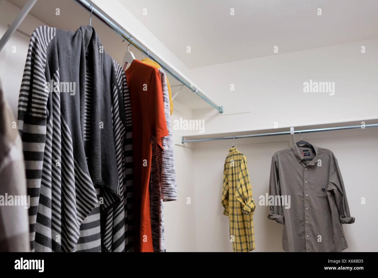 Un vestidor con camisetas de manga corta del hombre y la mujer suéteres y bufandas. Foto de stock