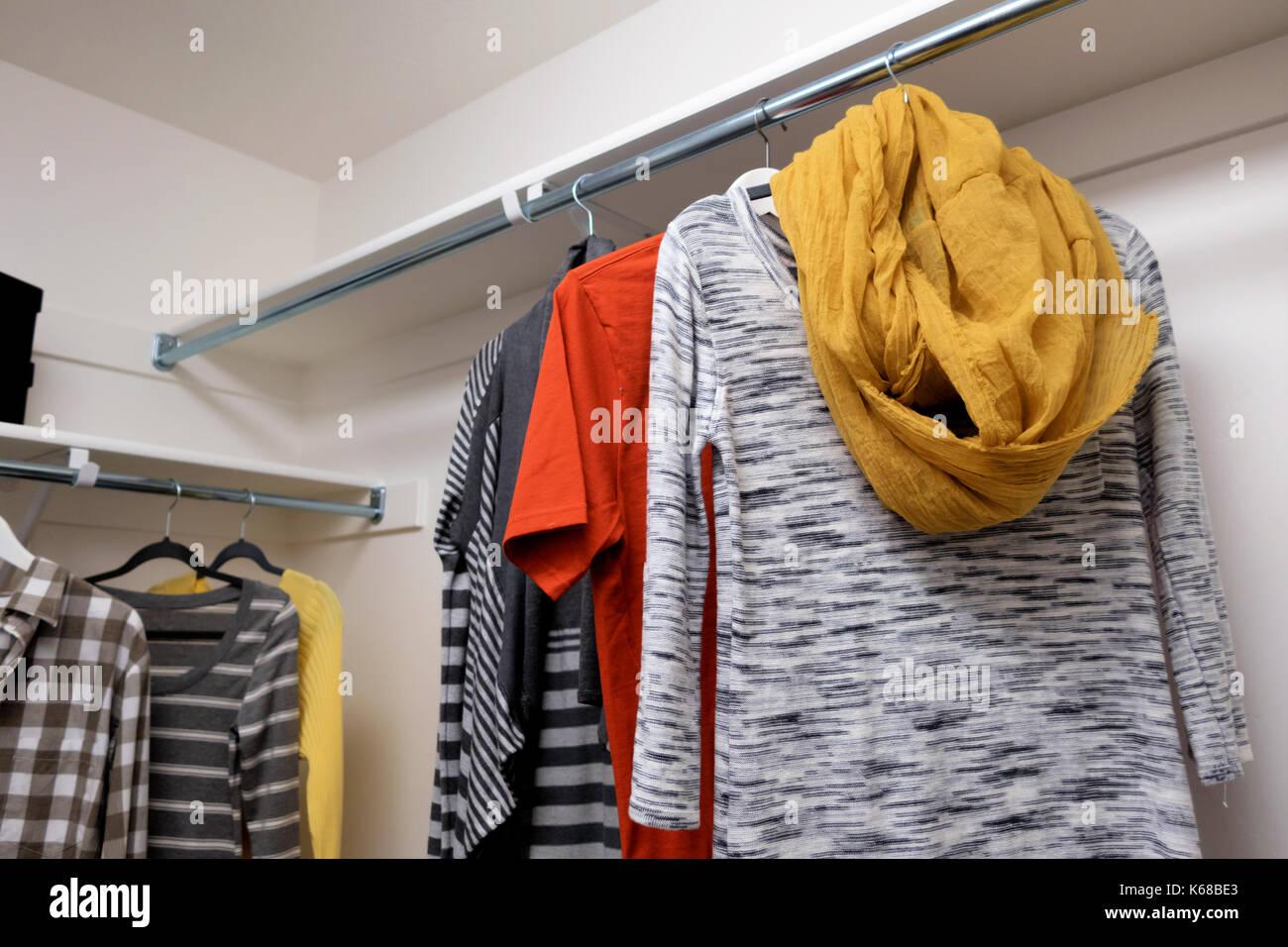 Un vestidor con camisetas de manga corta del hombre y la mujer suéteres y bufandas. Imagen De Stock