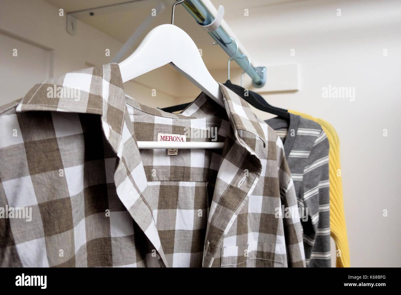 Un rack de los hombres camisetas de manga corta y womans suéteres. Imagen De Stock