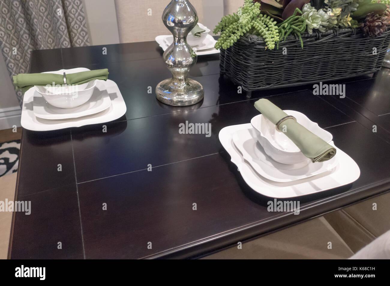 Configuración lugar alrededor de una mesa de comedor marrón con cuencos y servilletas verdes establecidos. Imagen De Stock
