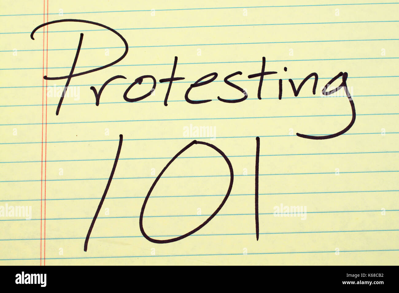 Las palabras 'protestando 101' en un bloc de notas de papel amarillo Imagen De Stock