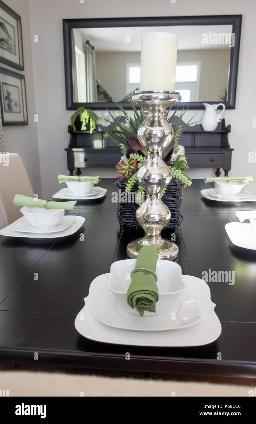 Mirando hacia abajo en una mesa de comedor marrón en lugar ajustes con cuencos un servilletas verde establecidos. Imagen De Stock
