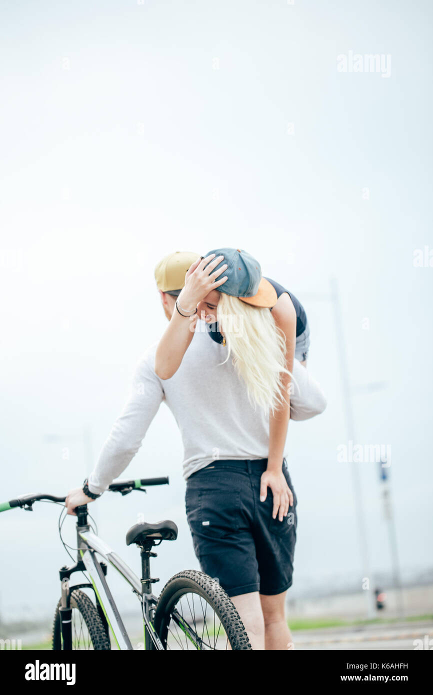 Pareja sonriente en un día de verano, Guy manteniendo a su novia en el hombro. Imagen De Stock