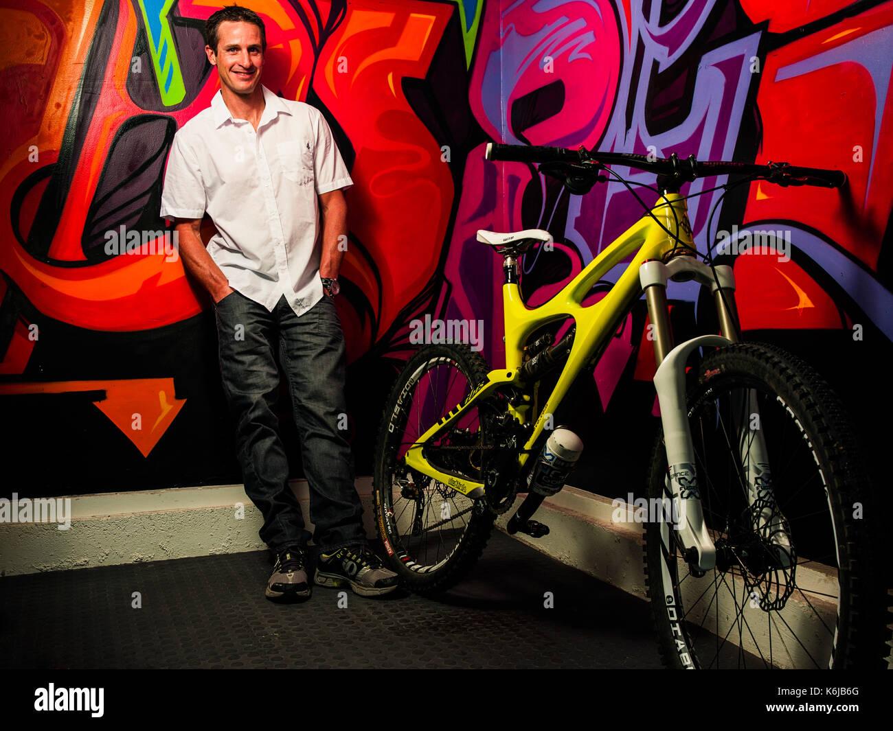 Hombre de pie en el interior junto a bicicleta y pared cubierta con graffiti, Laguna Beach, California, EE.UU. Imagen De Stock