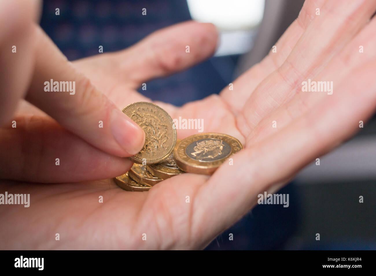Sacando una vieja moneda libra de un puñado de nuevas monedas libra Imagen De Stock