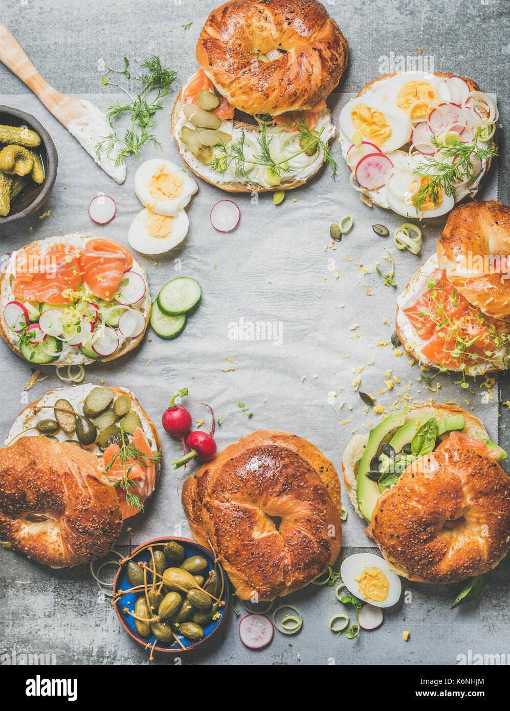 Variedad de bagels frescos con diferentes rellenos, espacio de copia Foto de stock