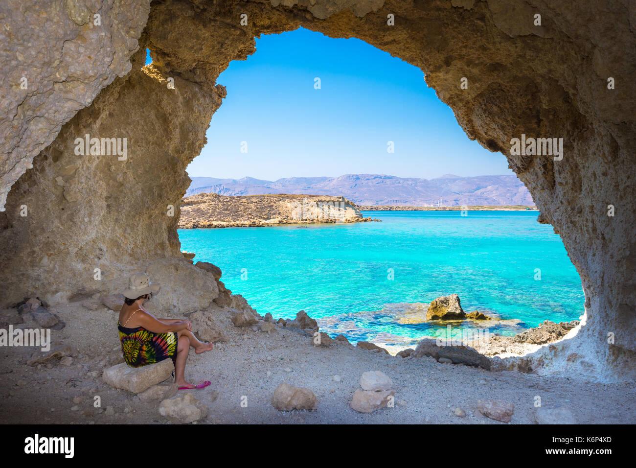 Increíble vista de verano de mujer en una cueva en koufonisi isla mágica con aguas color turquesa, lagunas, Imagen De Stock