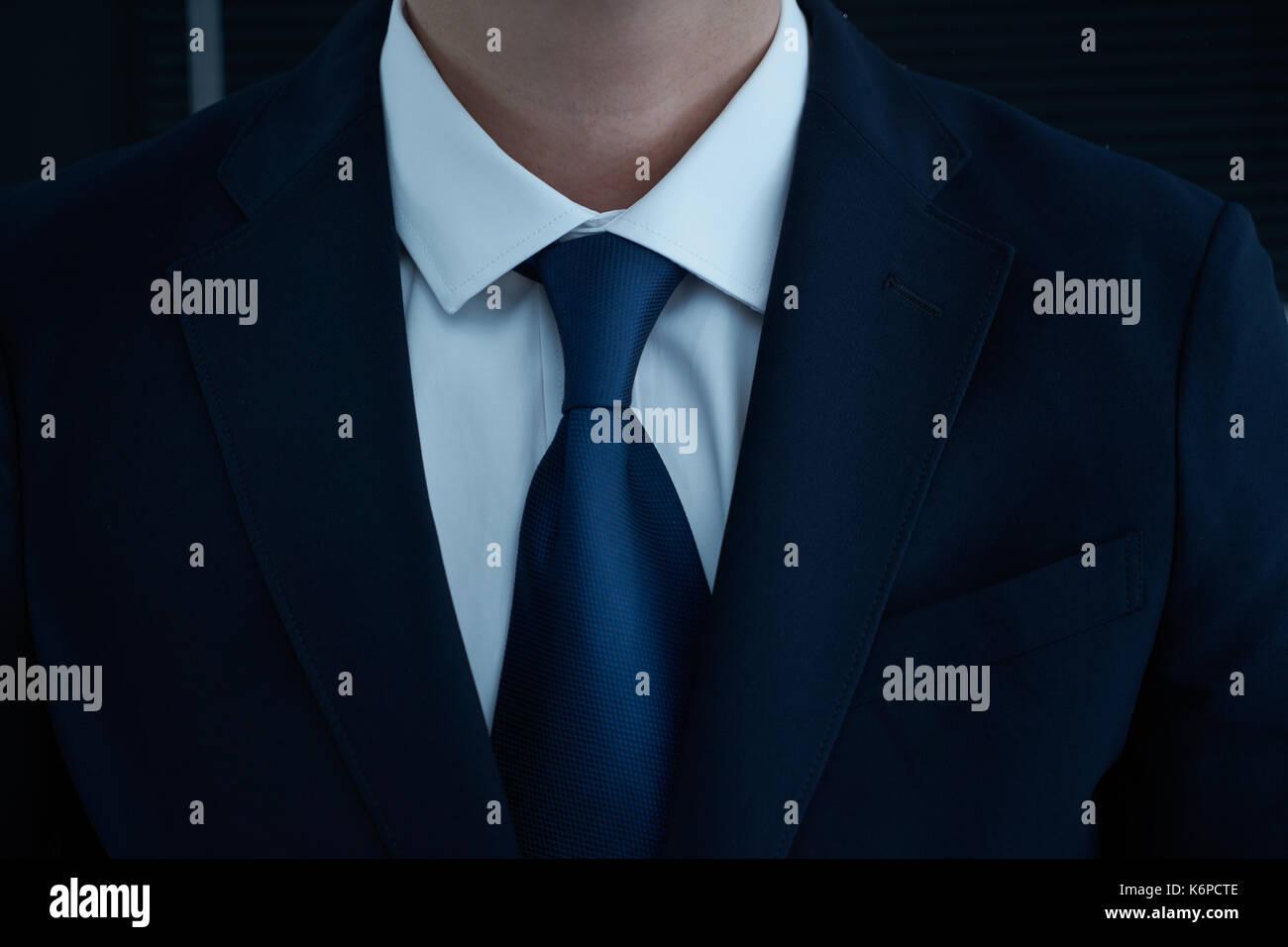 Parte lateral del cuerpo del hombre los brazos plegados en traje negro sobre fondo negro, concepto de negocio . Imagen De Stock