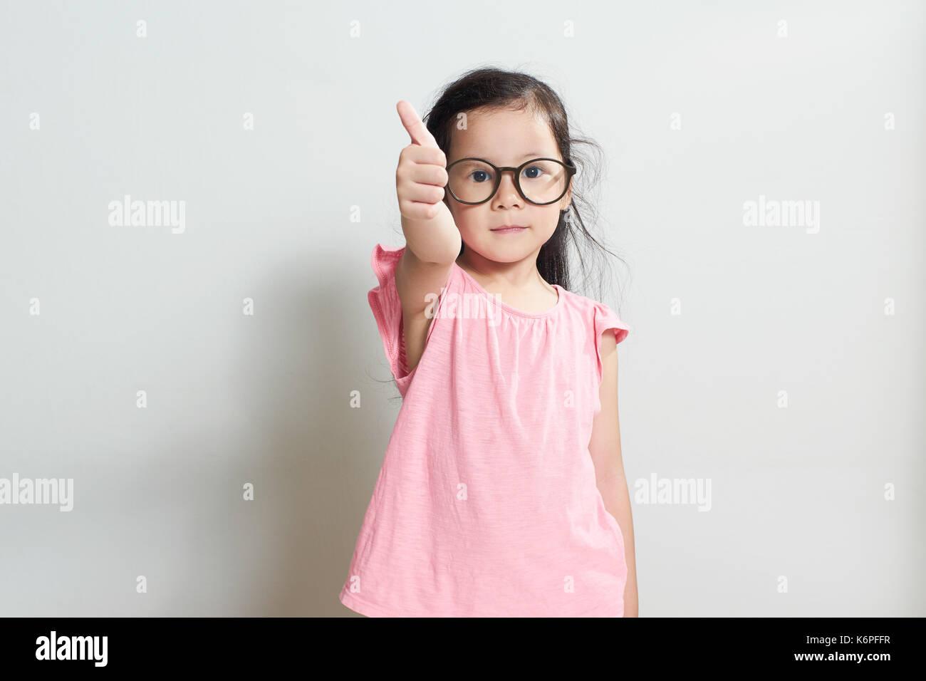 Niña vestida de rosa está mostrando el pulgar hacia arriba , gestos aislados sobre fondo blanco . Imagen De Stock