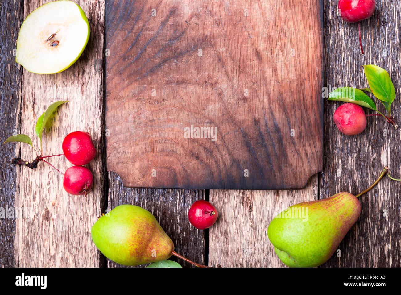 De pera y manzana pequeña alrededor del vacío en la tabla de cortar de madera fondo rústico. vista desde arriba. bastidor. cosecha otoñal. Copie el espacio Imagen De Stock