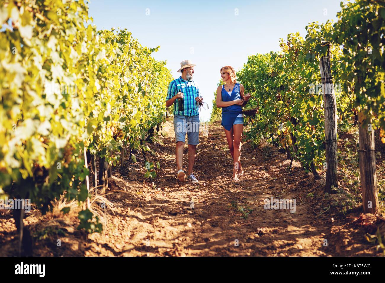 Hermosa pareja sonriente caminando a través de un viñedo y degustación de vino. Imagen De Stock