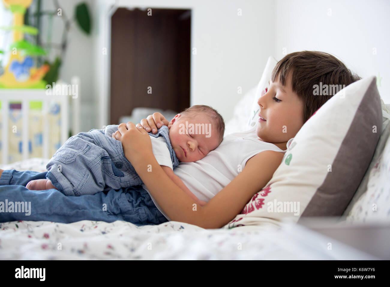 Hermoso muchacho, abrazando con ternura y el cuidado de su bebé recién nacido hermano en casa. La familia felicidad amor concepto Imagen De Stock