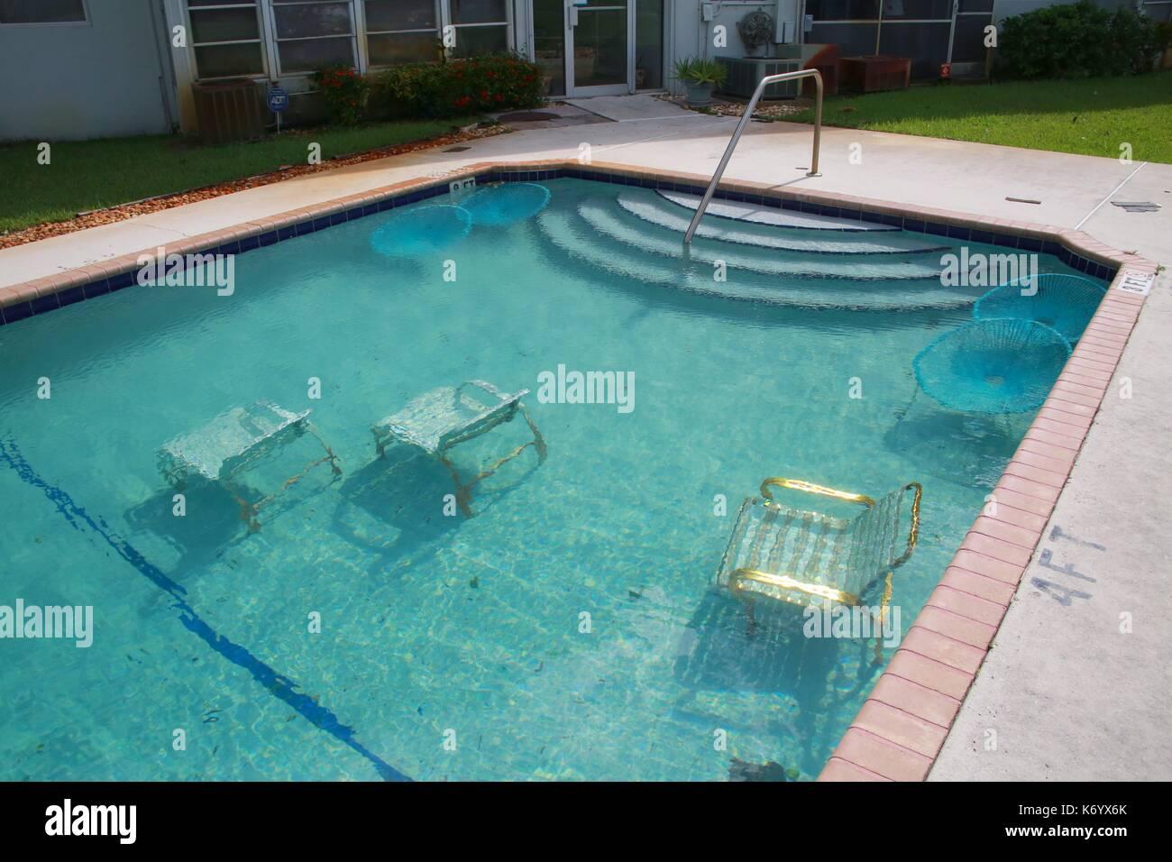 Muebles de cubierta en Crystal Lake condominiums intencionalmente sumergido en una piscina para mantenerla de soplar Foto de stock