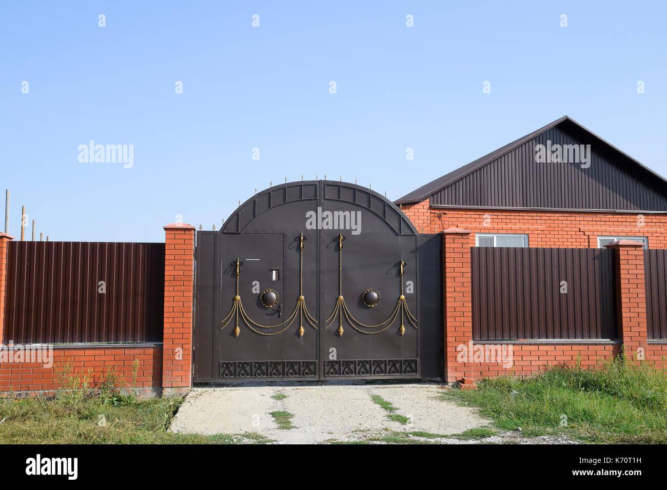 Casa de ladrillo con un cerco y portones vista de una for Cerco una casa in regalo