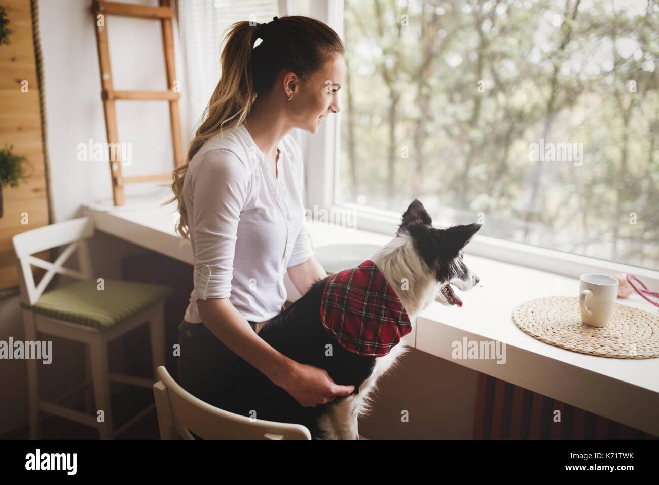 Bella mujer feliz mientras pasar tiempo con su perro en casa Imagen De Stock