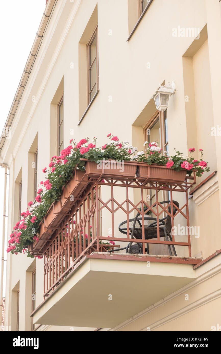 Pequeño y acogedor balcón con muebles de exterior, iluminación y flores. Imagen De Stock