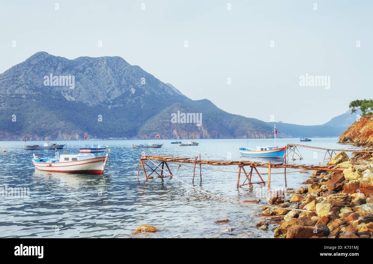 Botes cerca del muelle roto, poniendo en una apacible calma agua de mar azul Imagen De Stock