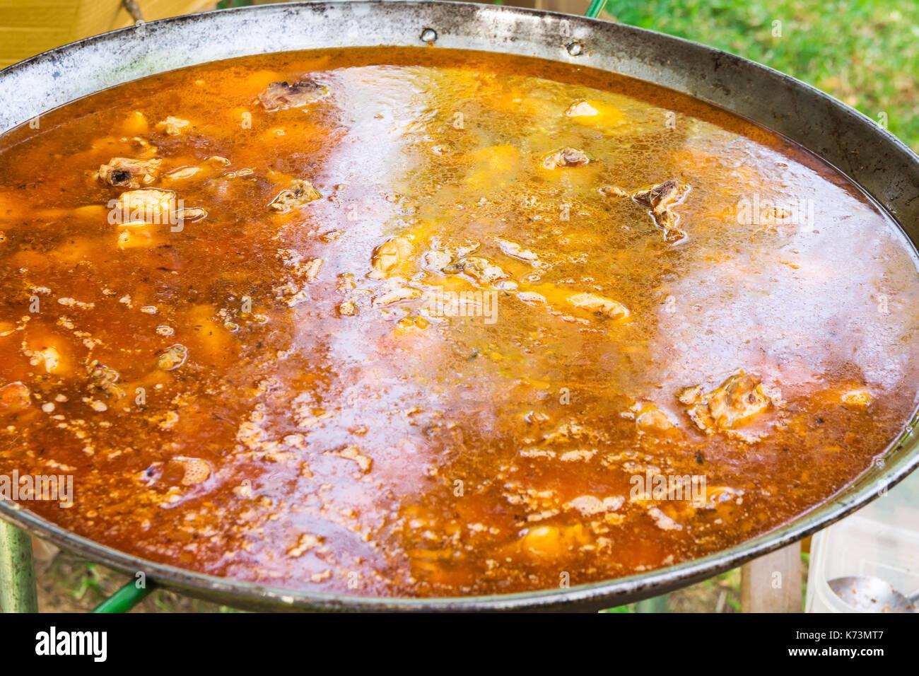 Proceso de cocinar paella valenciana o española jambalaya en sartén plana grande. Ingredientes carnes, arroz, legumbres, especias simmering en caldo con Foto de stock