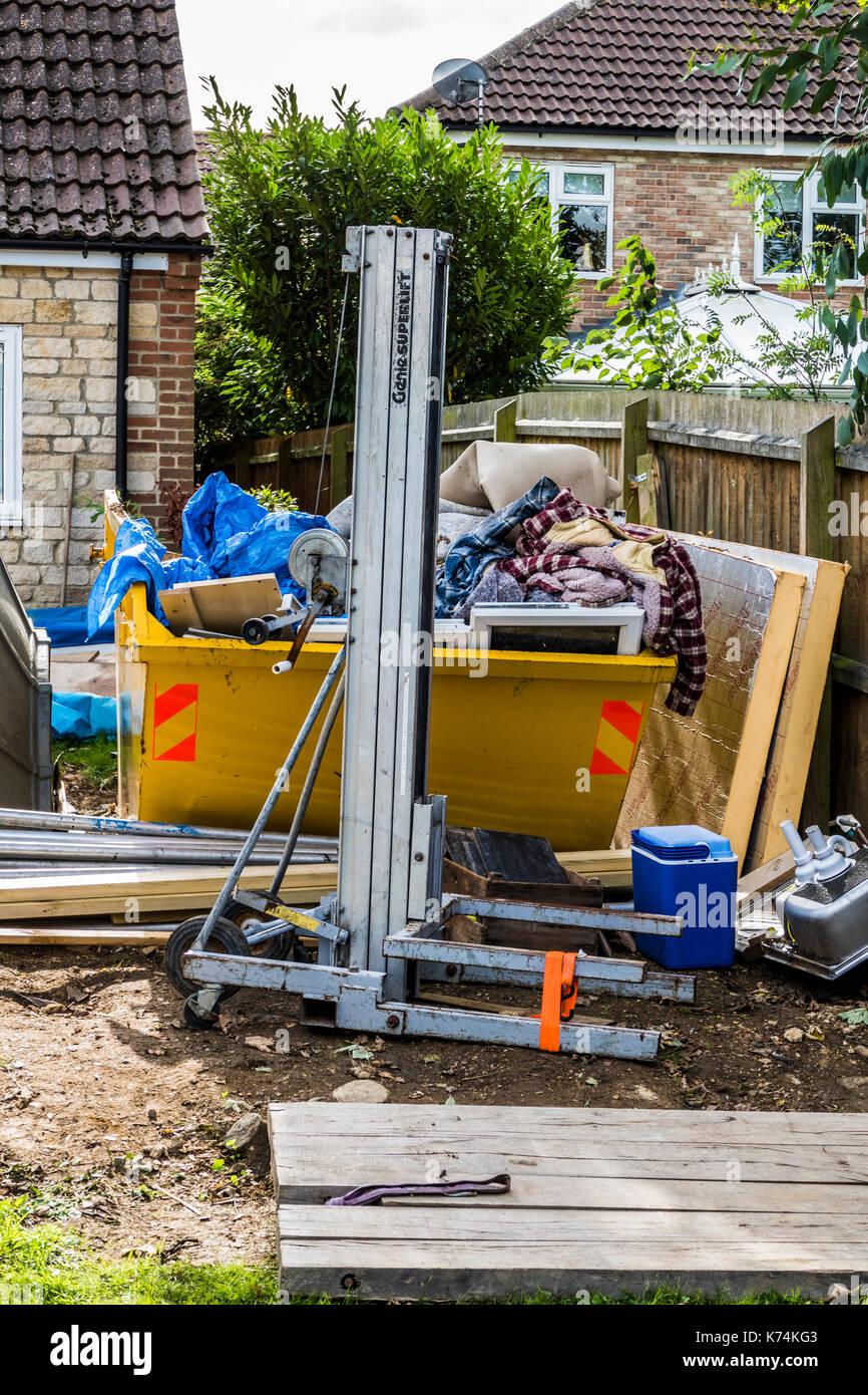Un gran contrató a saltar en el jardín de una casa, lleno de residuos de materiales relativos a un proyecto de construcción de hogares. Inglaterra, Reino Unido. Imagen De Stock