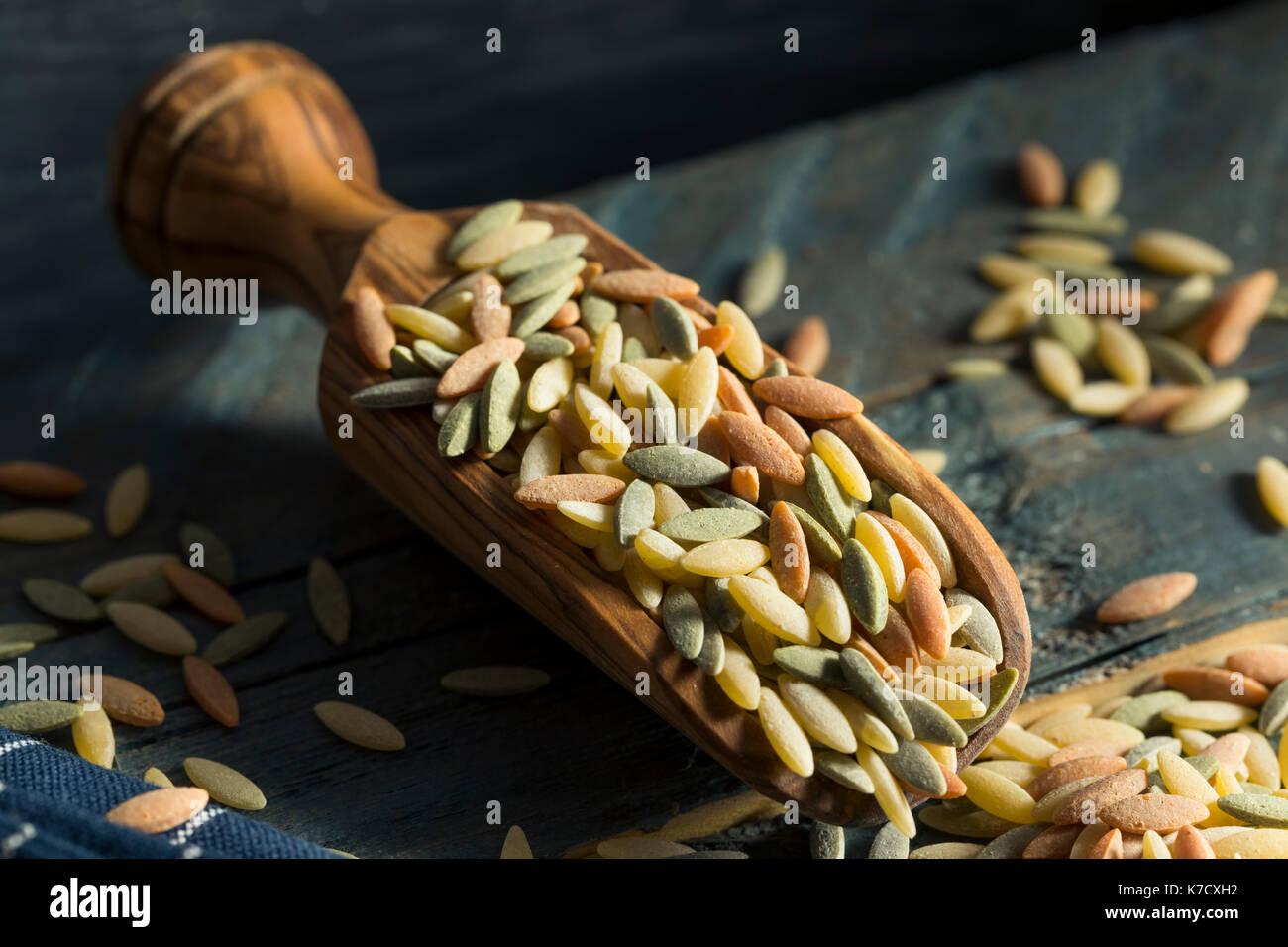 Tricolor pasta orzo orgánicos secos en un tazón Imagen De Stock