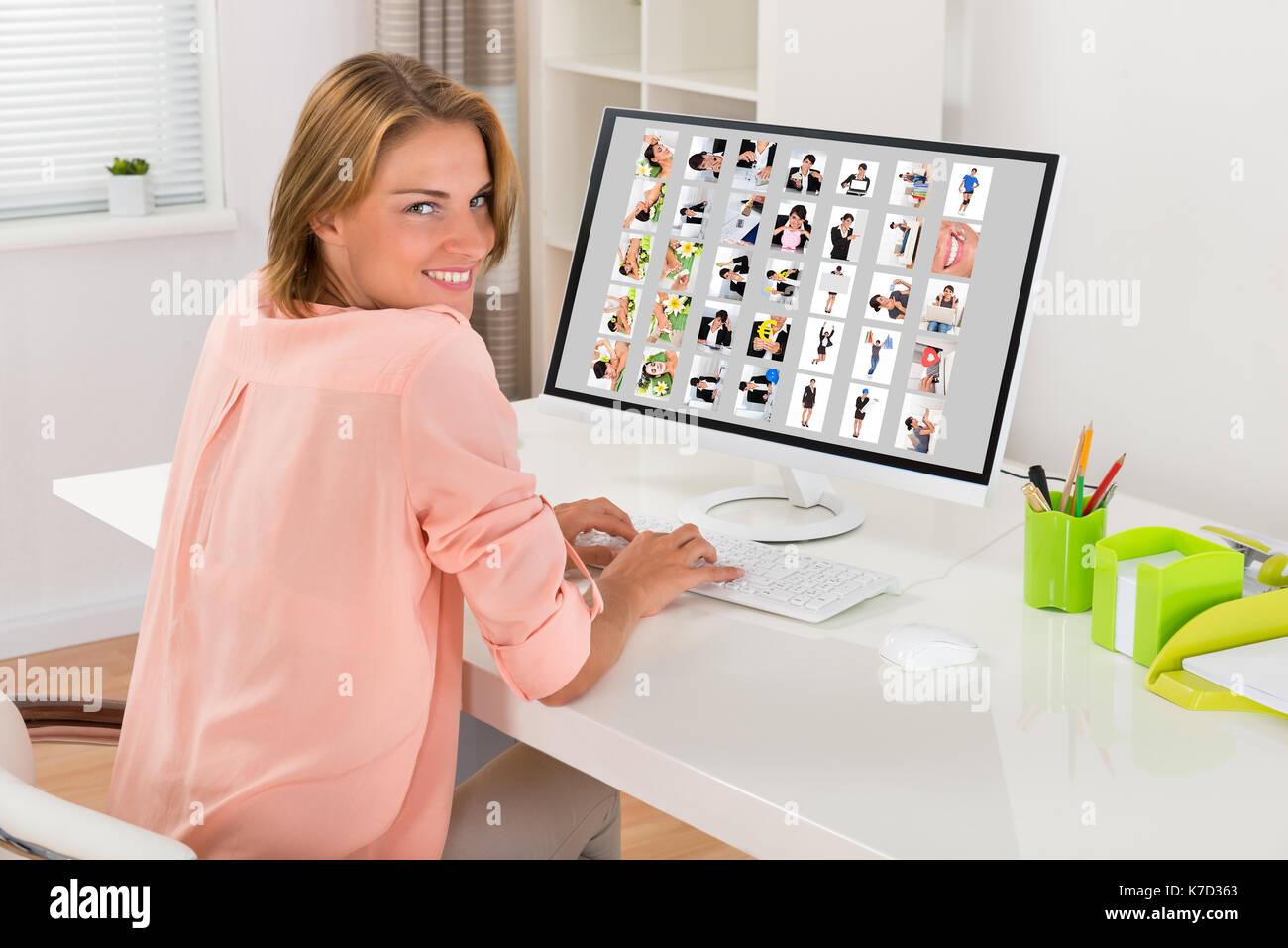 Feliz joven editora trabajar con fotos en el equipo de Office Foto de stock
