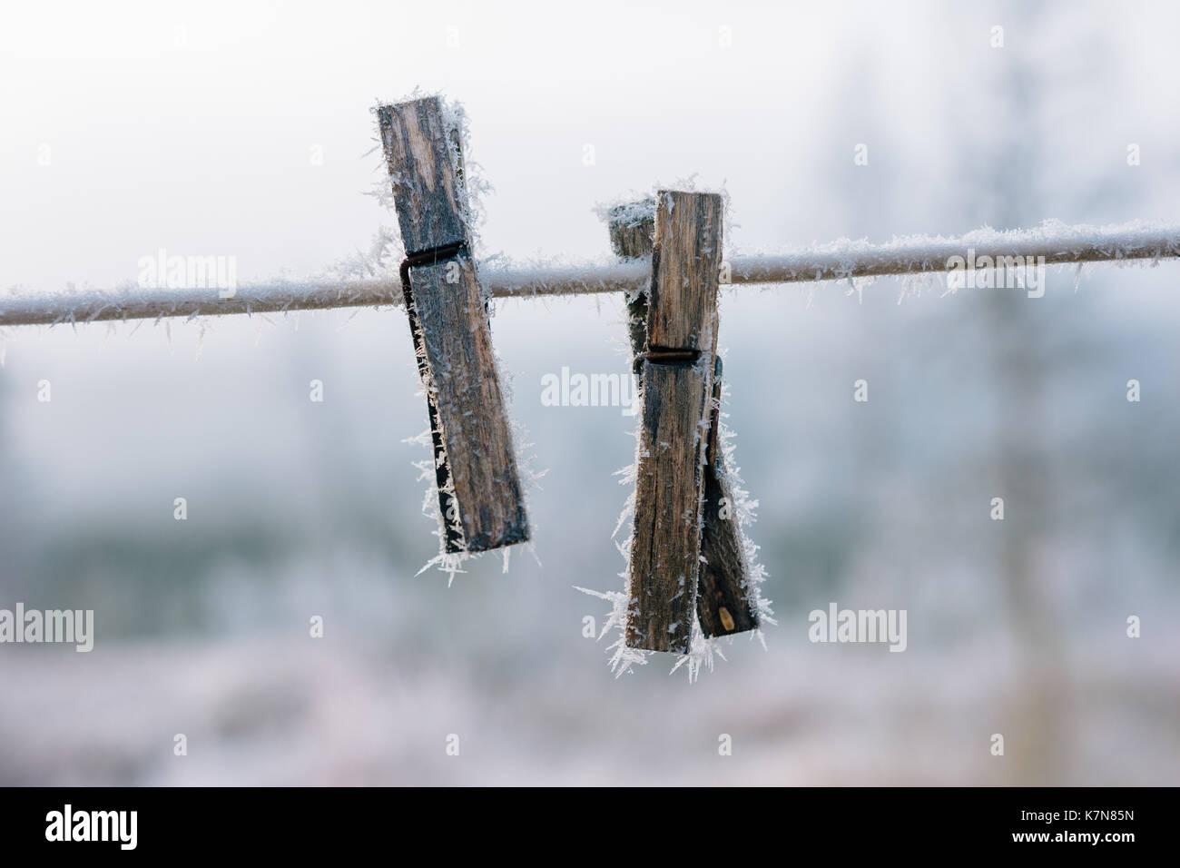 Dos clavijas de ropa cubierto con hielo al aire libre en una línea Imagen De Stock