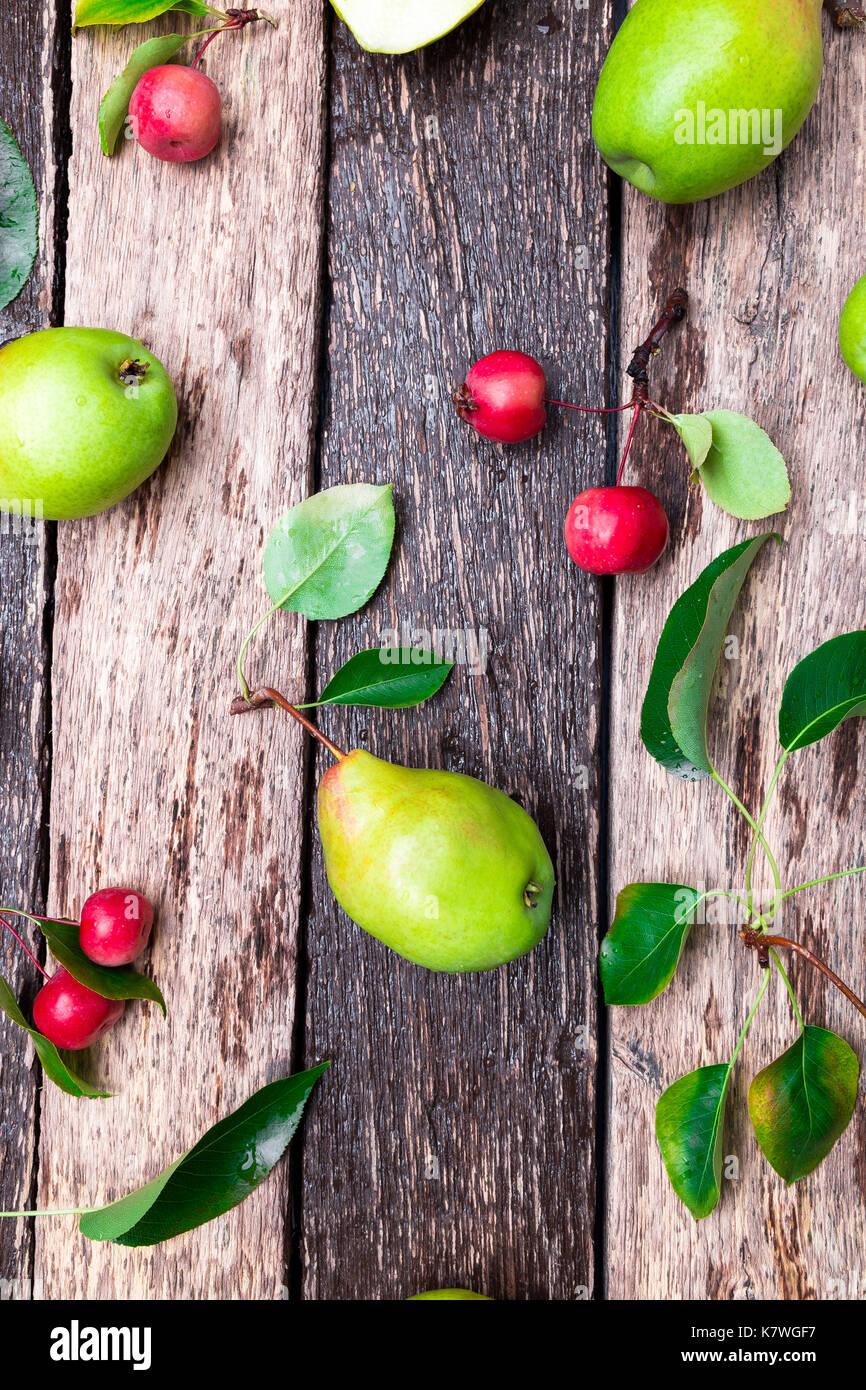 De pera y manzana pequeña sobre fondo rústico de madera. Vista desde arriba. bastidor. cosecha otoñal. Imagen De Stock