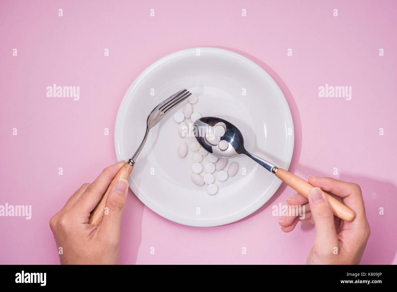 Vista superior de las manos del hombre en la mesa de comedor sosteniendo un tenedor y cuchillo encima del plato con píldoras sobre fondo de color rosa. Imagen De Stock