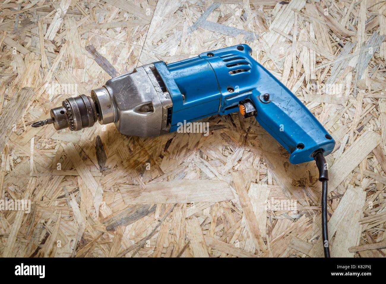 Casco azul-taladro destornillador cerca en una superficie de madera. Foto de stock