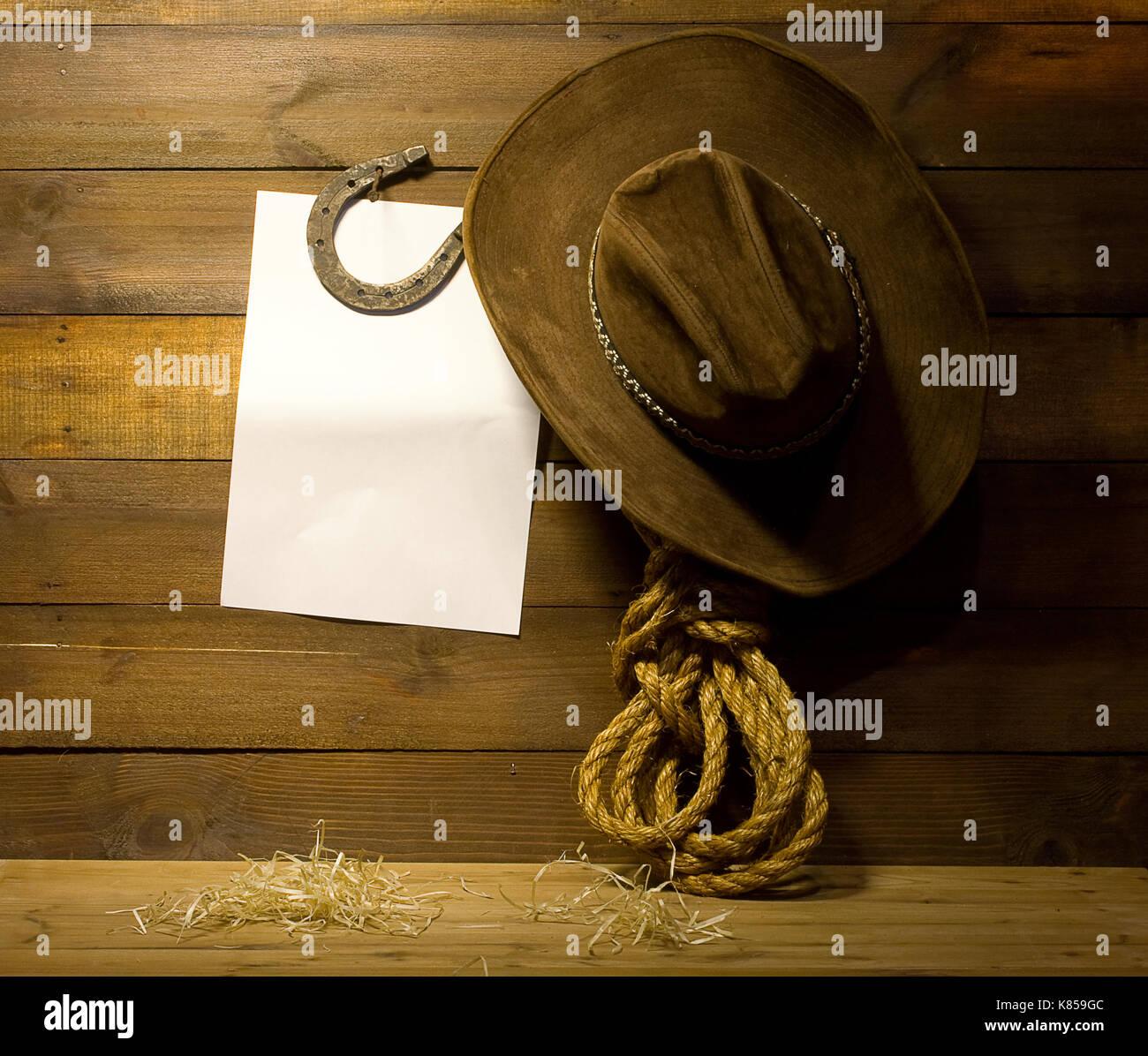 2bdb165541a3 Accesorios vaqueros colgados en la pared del rancho de madera antigua y de  fondo para el texto en blanco