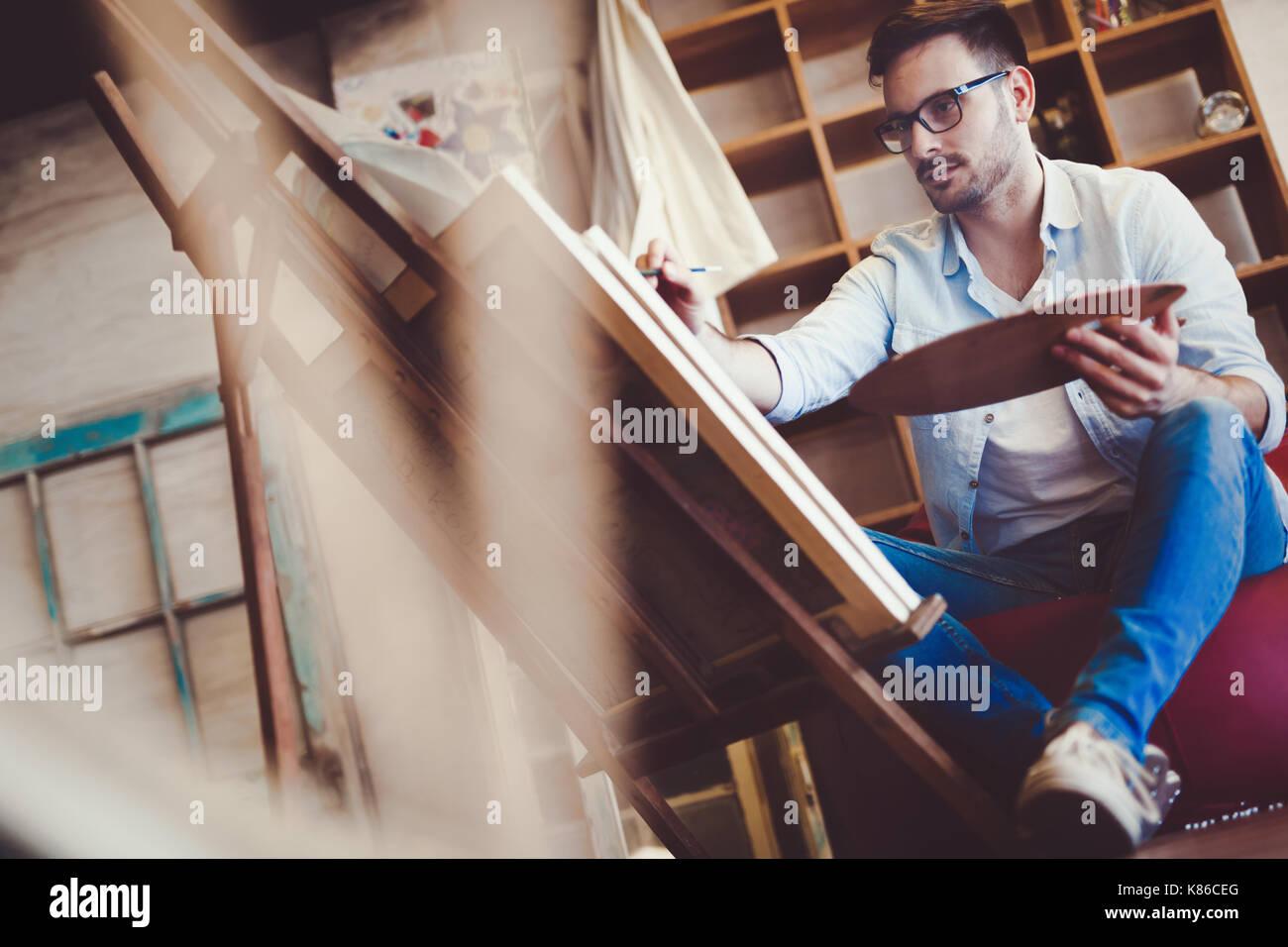 Escuela de arte masculino pintando con óleo sobre lienzo Imagen De Stock