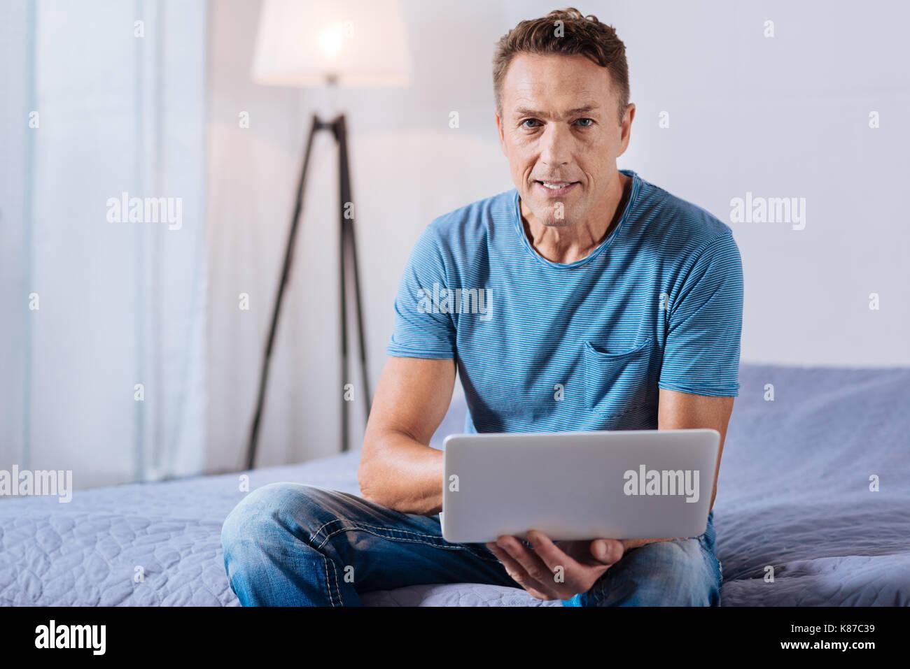 Guapo trabajando en el portátil en la habitación Imagen De Stock