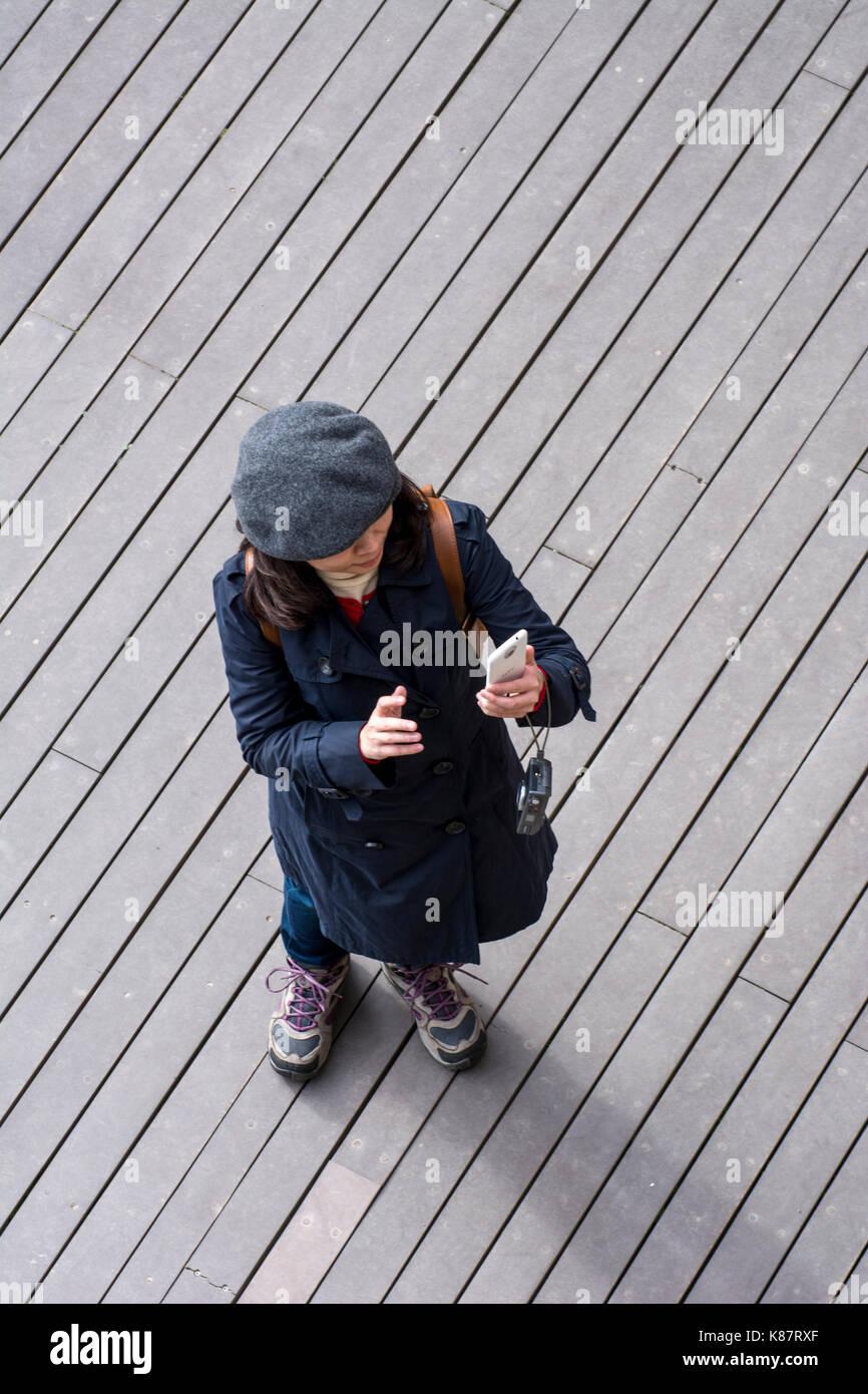 Un turista francés chica con sombrero tomando fotografías sobre un piso de madera en el Lago Ness, Escocia Imagen De Stock