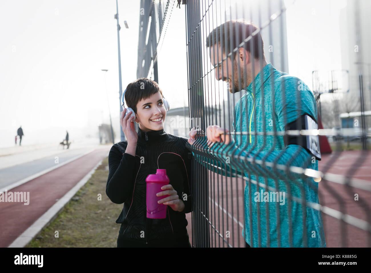 Deportista y sportswoman coqueteo outdoor fitness después de desempeño Foto de stock