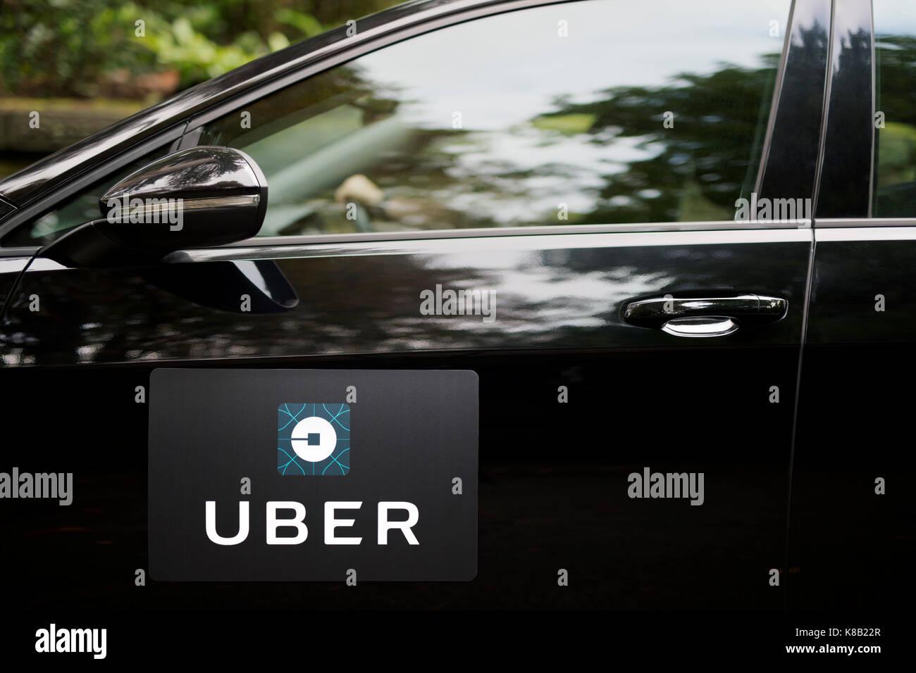 Un Volkswagen negro con el logotipo de Uber se utiliza como un taxi, y también muestra un controlador en una Imagen De Stock