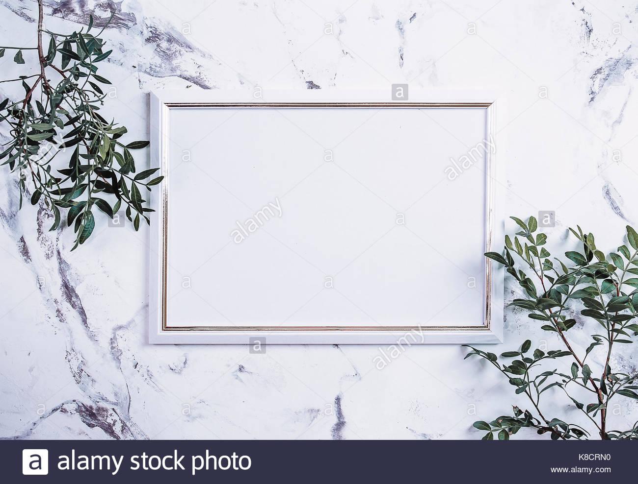 Marco de fotos en blanco y planta verde sobre un mármol de fondo de ...