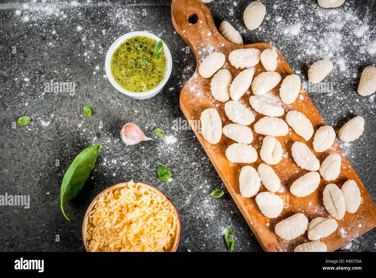 Raw casero sin cocer los ñoquis de patata con harina, queso parmesano rallado, la albahaca y la salsa pesto. Imagen De Stock