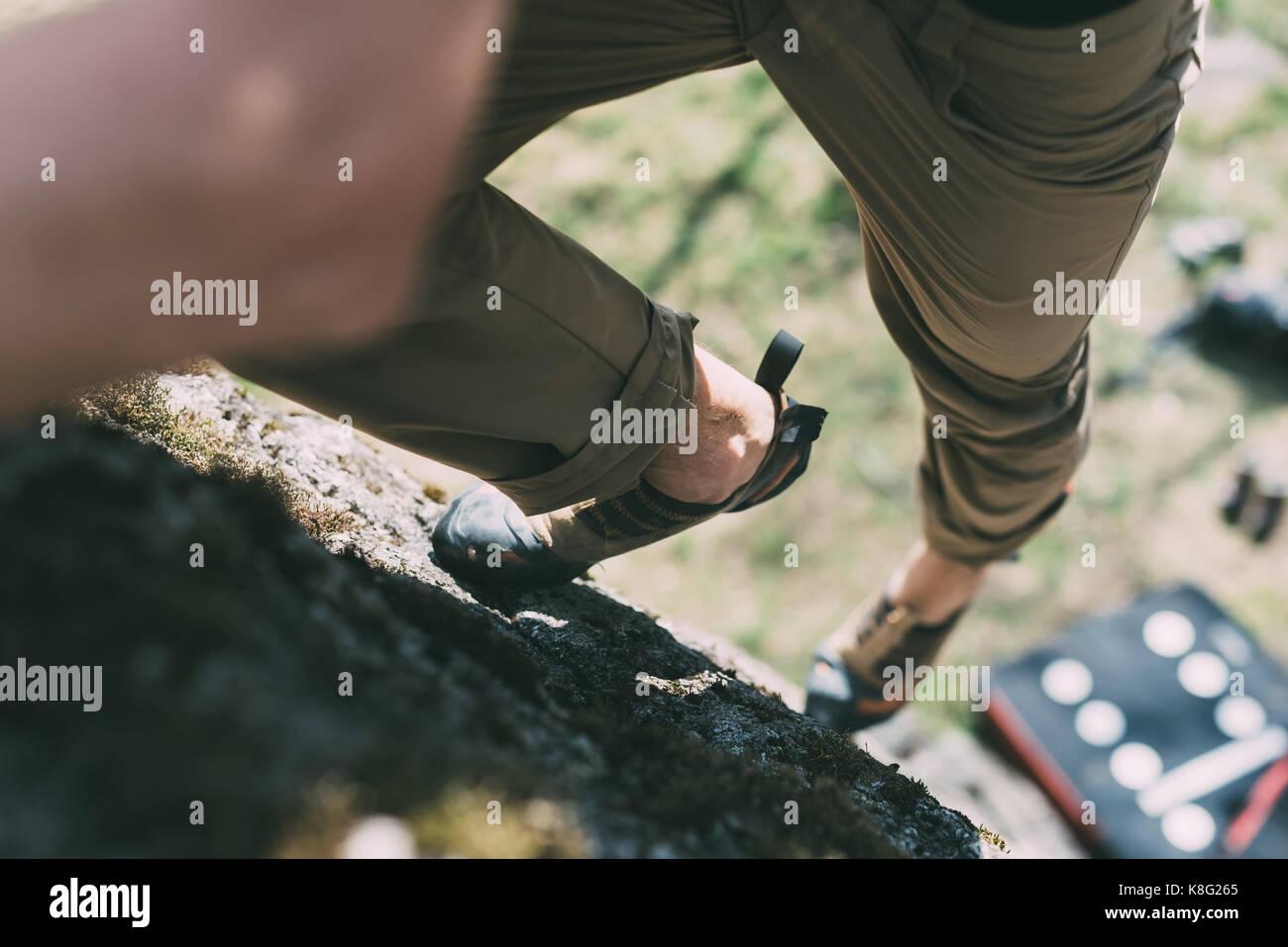 Vista de cintura para abajo boulderer macho subiendo boulder, Lombardía, Italia Imagen De Stock